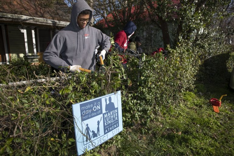 Martin Luther King Jr. (MLK) Day of Service Students volunteers manicuring a yard