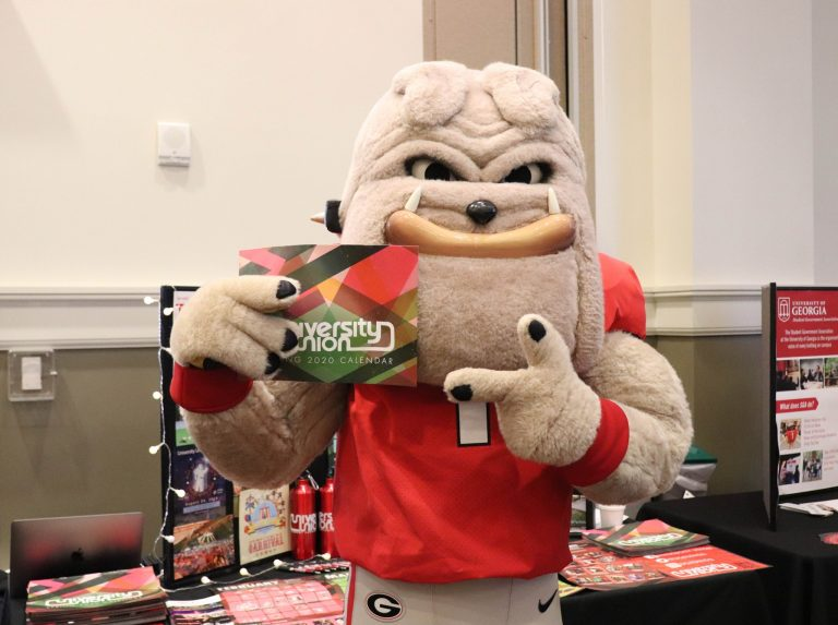 UGA mascot posing with a Student Union flyer